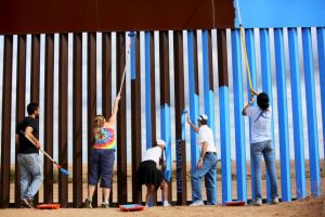 Volunteers Dan Watman, Brooke Collins, Maria Teresa Fernandez, Genaro Fernandez and Ana Lucia Lopez paint the border fence between the United States and Mexico to give it the illusion of transparency. REUTERS/Sandy Huffaker